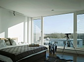 Sunny bedroom in white and warm grey tones with breakfast tray and telescope in front of large window