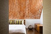 Doppelbett mit gestreiften Zierkissen, edle Holztruhe und Urne mit geometrischen Mustern unter Backsteinschräge