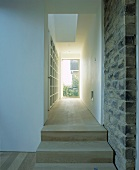 Wooden stairs next to a stone wall leading to a narrow room with shelving opening to a gallery above and with a glass door at the end