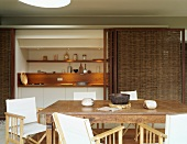 Antique wooden table and director's chairs in front of niche with small kitchen counter and bamboo sliding doors