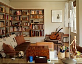 Youthful living room in natural colours with bookcases, guitar and artist's mannequin next to modern table lamp with transparent shade