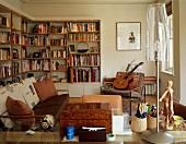 Jugendliches Wohnzimmer in Naturfarben mit Bücherwänden, Gitarre und Modulor neben moderner Tischlampe mit durchsichtigem Schirm