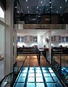 Brücke aus beleuchteten Glasbausteinen zwischen spiegelnden Glasflächen mit Blick auf Wohnraum