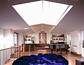 Long living room with skylight, bright blue upholstered furniture, grand piano and bar in back corner