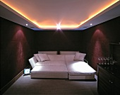 Indirect ceiling lights above wide sofa bed and bar with wine glasses in bordeaux-coloured bedroom