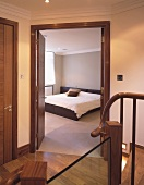 Uniform wood colour of doors, floors and stairs in hallway with view of grey bedroom