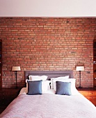 Double bed with upholstered head and scatter cushions flanked by graceful bedside lamps in front of brick wall