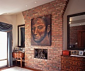 Antique chests of drawers and mirrors on both sides of brick-clad chimney breast with large portrait