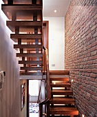 Two flights of stairs next to exposed brickwork wall with spotlights in English house