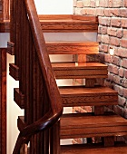 Wooden living room stairs ornamented with double grooves next to an exposed brick wall with recessed spotlights