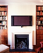 White wall with flat-screen over open fireplace flanked by traditional bookcases