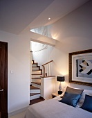 Traditional bedroom with modern painting in antique frame next to winding wooden staircase to ensuite bathroom