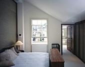 Modern bedroom with ensuite bath, English lattice sash window and storage bench