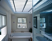 Light and shade effect through horizontal blinds covering large skylight in modern bathroom with English sash windows