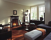 English living room with fire in fireplace, sofas, ottomans, easy chairs and retro table