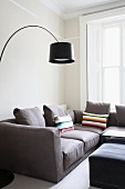 A modern living room corner - a curved lamp with a black shade above a light grey sofa