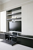 A modern living room cupboard with a flat screen television and a stereo cupboard