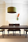 A classic-modern dining room with a retro pendent lamp about a dark wooden table