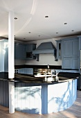 A curved kitchen counter with a sink in a country house-style kitchen