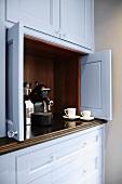 An espresso machine in a kitchen dresser with open doors