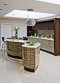 Designer kitchen with curved kitchen island in front of fitted kitchen and suspended ceiling with cut-out section