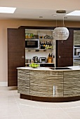 Curved kitchen island with glossy structured fronts in front of open refrigerator