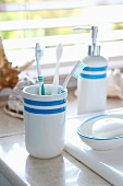 Beaker with toothbrushes and soap dish on washstand