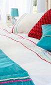 Various coloured cushions on a bed