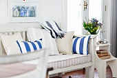 White painted bench with cushions and striped upholstery next to glass door