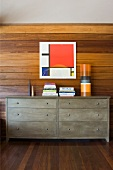 Chest of drawers with books in front of wood-panelled wall