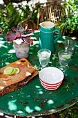 Gartentisch mit Limonade, Schneidebrett und Topfpflanze