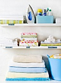 White shelves with ironed washing, iron and cleaning products