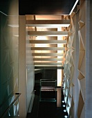 Back view of stairs in narrow stairwell with structured wall