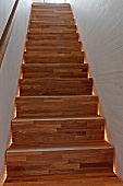 Narrow staircase with backlit wooden stairs