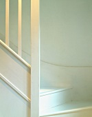 White stairwell, wooden stairs and balustrade