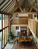 Open-plan house with dining area and views of gallery and rustic roof timbers