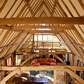 Rustic roof timbers and open-plan living space with wooden support structures