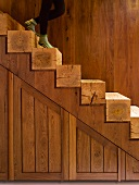 Partially visible person on open-plan wooden staircase with square timber steps in front of wooden wall