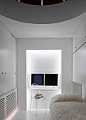 Weisses Gästezimmer mit Flokatidecke auf Bett und transparentem Plexiglasstuhl vor Fenster