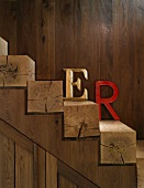 Coloured decorative letters leaning on wooden wall on square timber steps