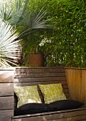 Bamboo flower bed with integrated wooden bench and cushions on terrace