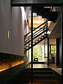 Open-plan stairwell with integrated, backlit sideboard in contemporary house