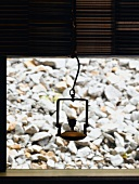 Metal vessel hanging in front of window and view of stones