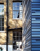 Facade with blue painted wooden slats in front of English house with brick facade