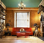 Animal trophies in rustic modern salon with orange sofa in front of wooden wall