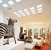 Animal trophy on pedestal in open-plan living room of villa