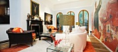 Antique leather armchair and light sofa in front of mural in living room of villa