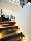 Recessed spotlights on rustic wooden steps leading to open-plan living room