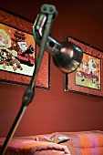 Chrome standard lamp in front of framed cartoons on a red wall