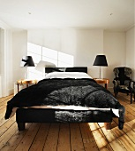 Frame of double bed and bedspread in black fur in white bedroom